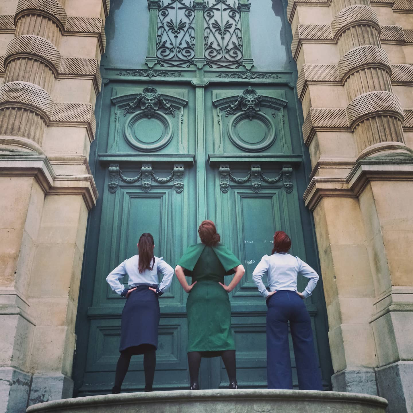 3 mannequins devant une grande porte